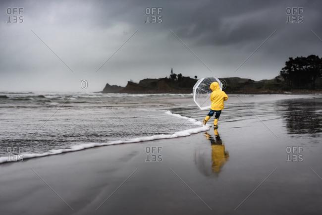 Boy by ocean with umbrella
