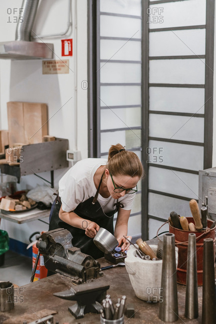 Female jeweller pouring liquid into jewellery mould at workbench