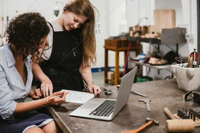 Two female jewellers drawing in notepad at workbench