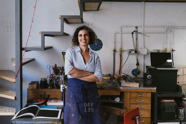 Portrait of smiling female jeweller in jewellery workshop