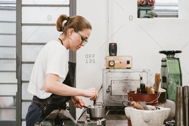 Female jeweller stirring saucepan in jewellery workshop