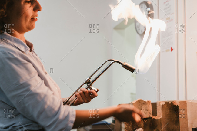 Female jeweller using flaming  blow torch at workbench