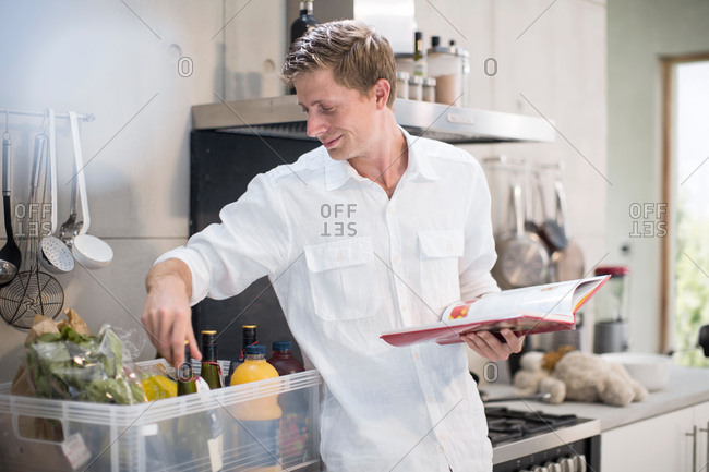 Man with recipe book, making preparations in kitchen