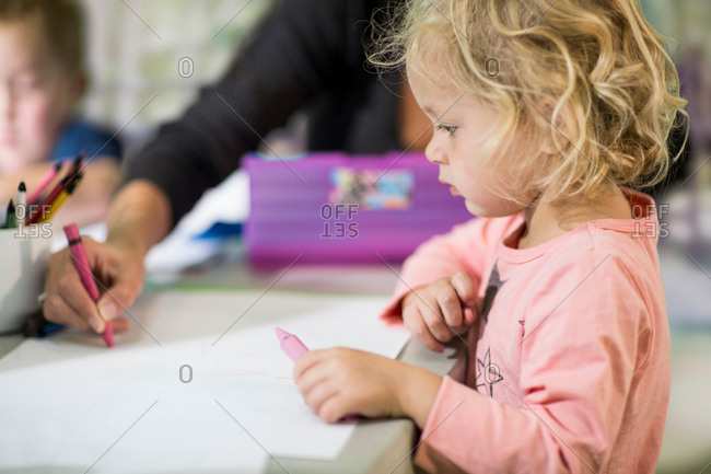 Teacher teaching girl to draw