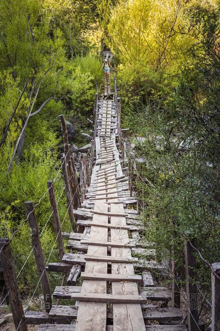 Female hiker crossing dangerous wooden footbridge at Cajon del Azul near El Bolson, Patagonia, Argentina