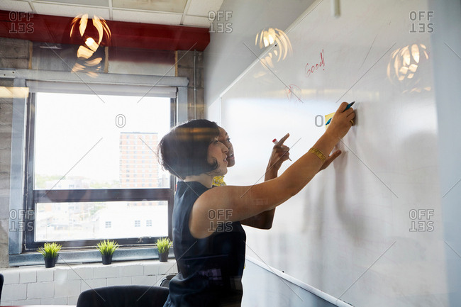 Two women in office, brainstorming, sticking sticky notes on whiteboard