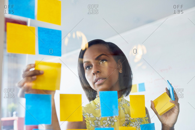 Young woman in office, sticking sticky notes to glass in office
