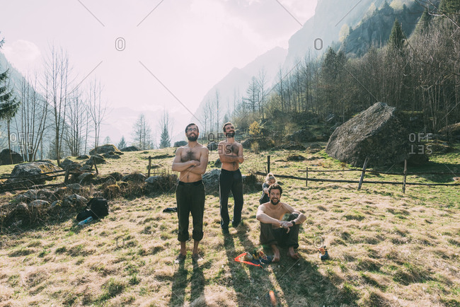 Four adult friends watching male bouldering from valley, Lombardy, Italy