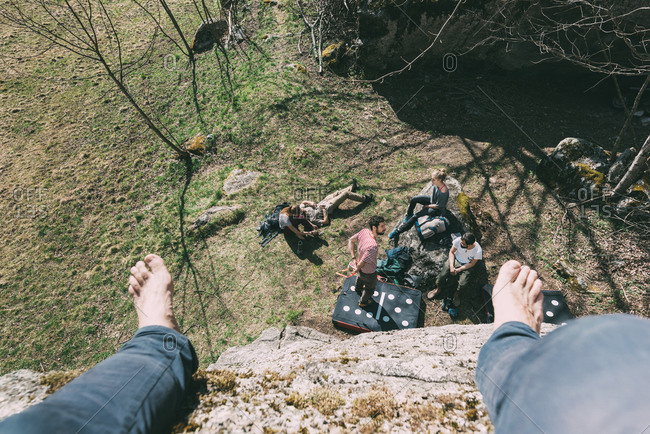 High angle perspective of boulderer above friends on boulder, Lombardy, Italy