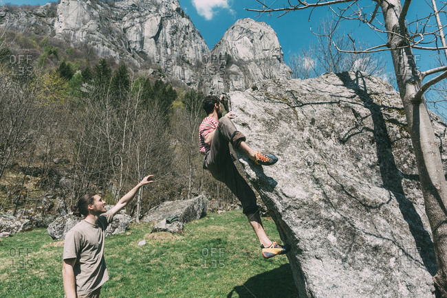 Young male boulderer pointing for woman climbing boulder, Lombardy, Italy