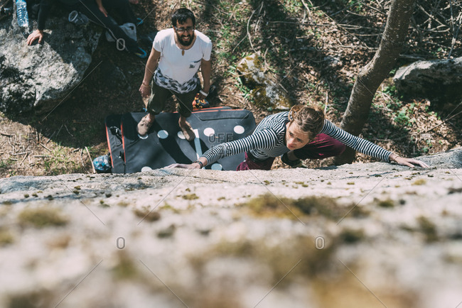 Overhead view of young female boulderer climbing boulder, Lombardy, Italy