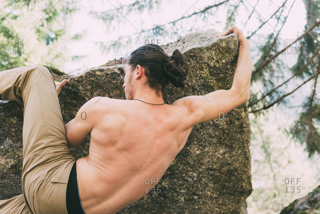 Rear view of bare chested male boulderer climbing boulder edge, Lombardy, Italy