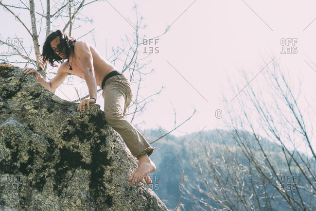 Bare chested and bare foot male boulderer climbing boulder, Lombardy, Italy
