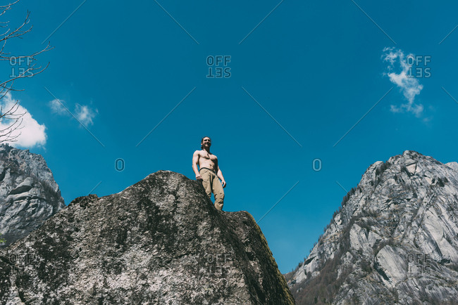 Low angle view of bare chested young male boulderer looking down boulder top, Lombardy, Italy