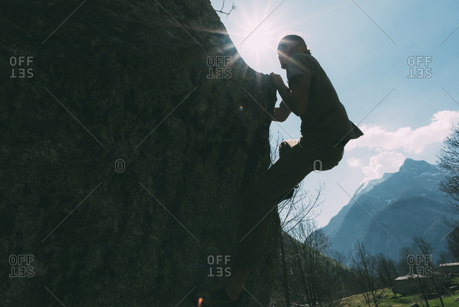 Backlit view of young male boulderer climbing boulder, Lombardy, Italy