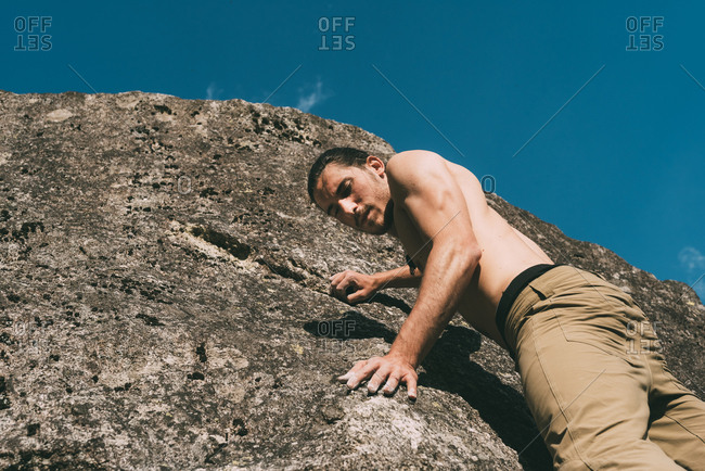 Low angle view of bare chested young male boulderer climbing boulder, Lombardy, Italy