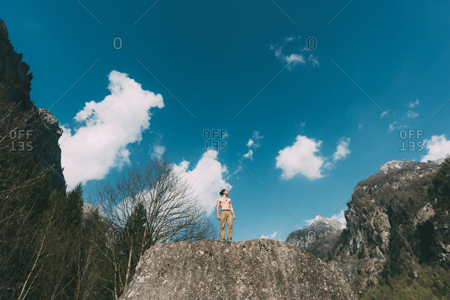 Low angle view of bare chested young male boulderer on boulder top, Lombardy, Italy