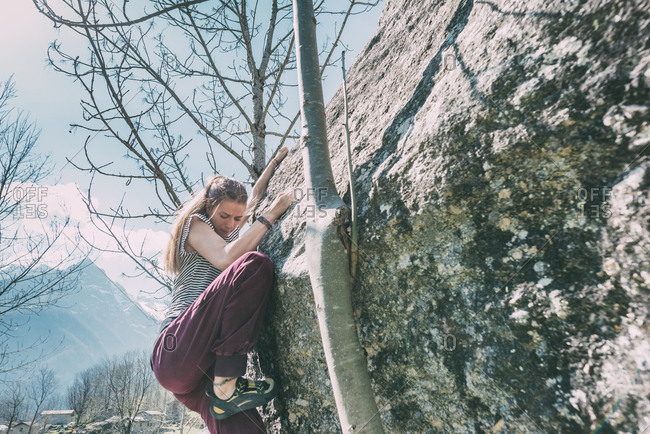 Young female boulderer climbing boulder, Lombardy, Italy