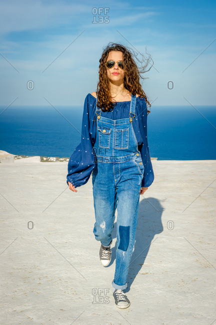 Girl in dungarees, sea and sky in background, O�a, Santorini, Kikladhes, Greece