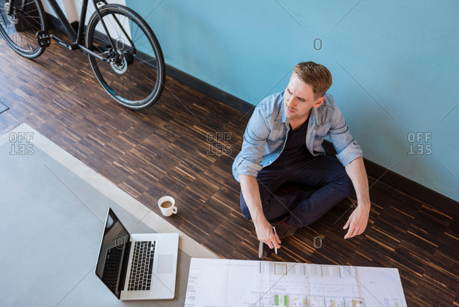 Male designer sitting on floor contemplating blueprint