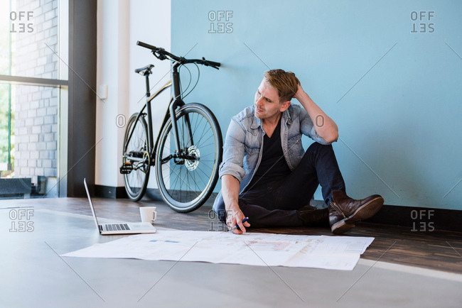 Male designer sitting on floor scratching head thinking about at blueprint