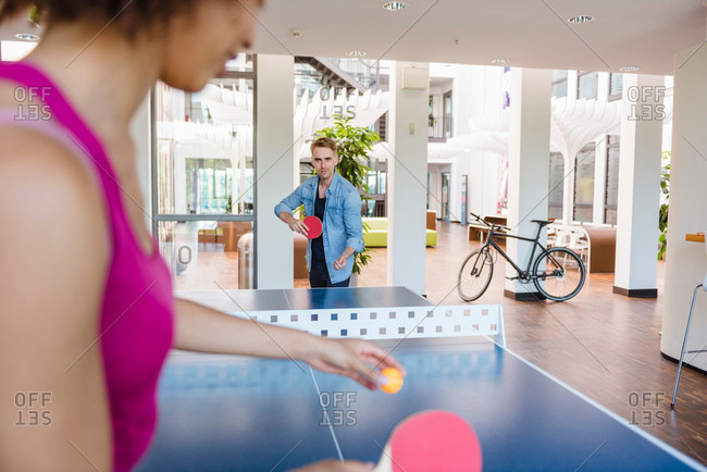 Over shoulder view of couple practicing table tennis in apartment
