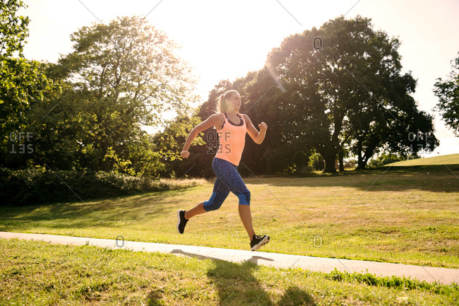 Young female runner running along park path in sunlight