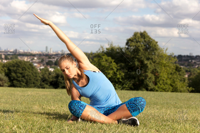 Young woman practicing yoga in park, sitting cross legged bending sideway