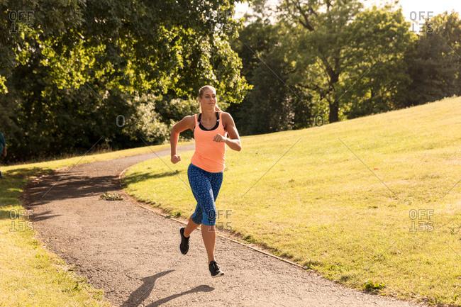 Young female runner running along park path