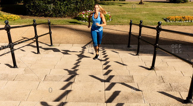 Young female runner running up park stairway