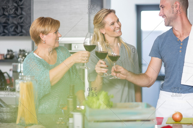 Three friends in kitchen, holding wine glasses, making a toast