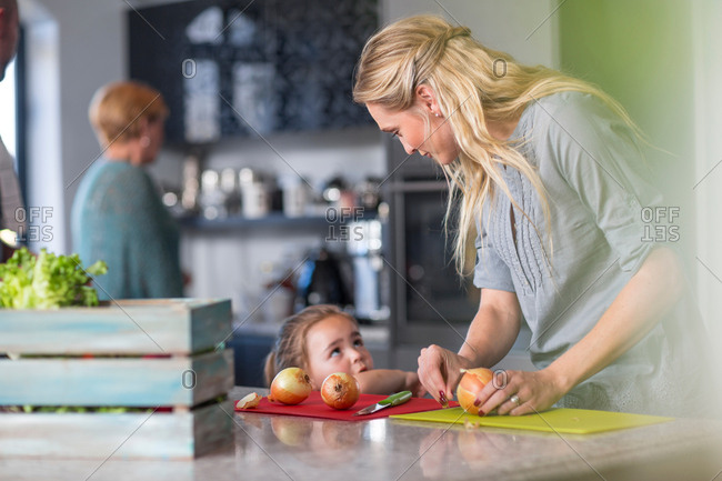 Woman preparing food in kitchen, young daughter standing at kitchen counter beside her
