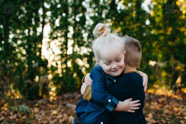 Cute female toddler hugging twin brother in autumn garden