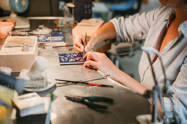 Female jeweller picking up silver metal with tweezers at workbench