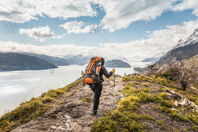 Rear view of female hiker hiking alongside Grey glacier lake, Torres del Paine National Park, Chile