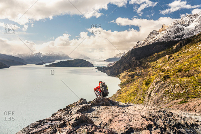 Male hiker crouching to look out over Grey Lake and Glacier, Torres del Paine national park, Chile
