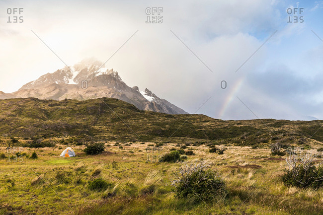 Mountain landscape with tent and rainbow, Torres del Paine national park, Chile