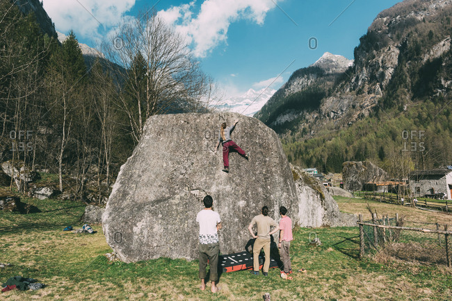 Rear view of adult bouldering friends watching young woman climb boulder, Lombardy, Italy