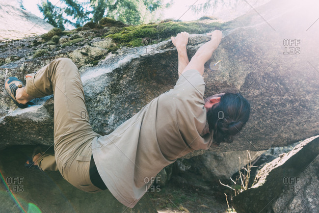 Young male boulderer climbing edge of boulder, Lombardy, Italy
