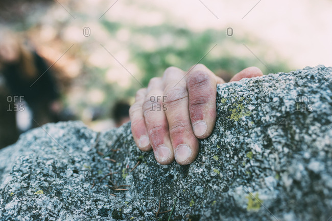 Hand of male boulderer gripping boulder edge, Lombardy, Italy