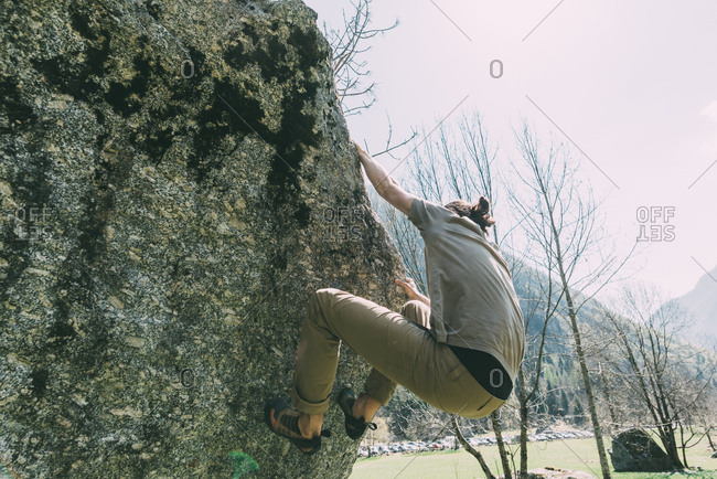 Young male boulderer climbing boulder, Lombardy, Italy