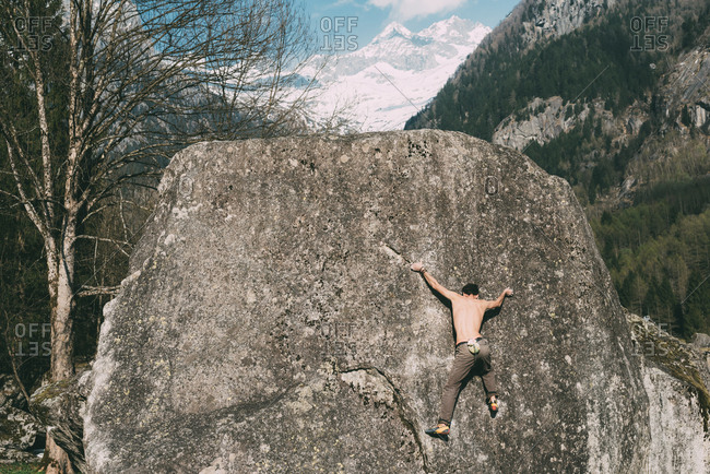 Rear view of young male boulderer climbing boulder, Lombardy, Italy