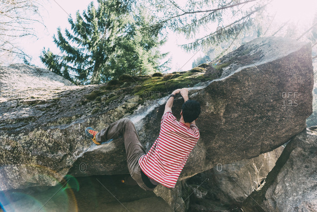 Male boulderer climbing boulder overhang, Lombardy, Italy