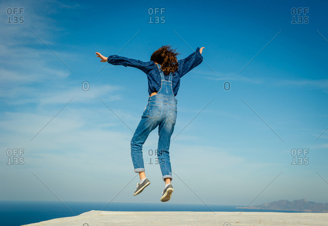 Girl in midair, sea and sky in background, O�a, Santorini, Kikladhes, Greece