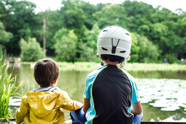 Two young brothers sitting at water's edge, older brother wearing cycling helmet, rear view