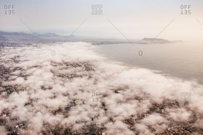 Aerial view of city and coast through cloudscape, Lima, Peru