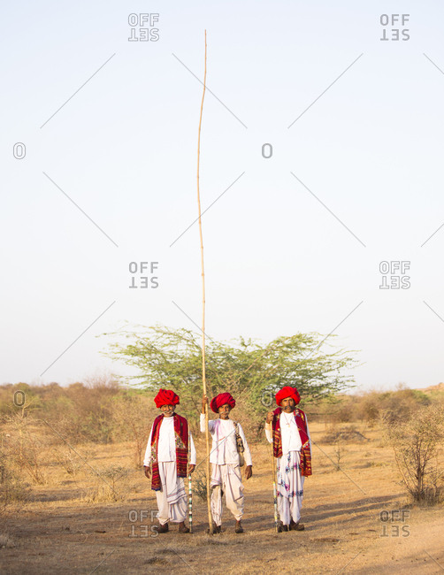Jawai, Rajasthan, India - May 19, 2015: Rabari herdsmen with their large stick to beat fruit out of trees
