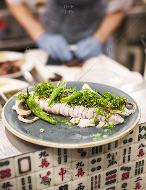 Hong Kong, China - November 16, 2015: Grilled squid with shishito peppers at Ho Lee Fook