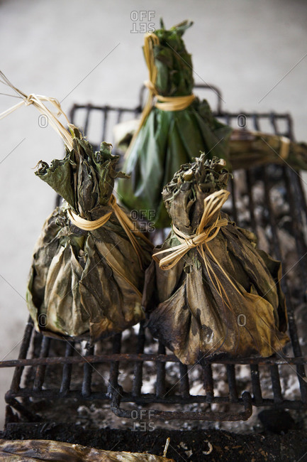 Plantain leaves stuffed and cooking on a grill