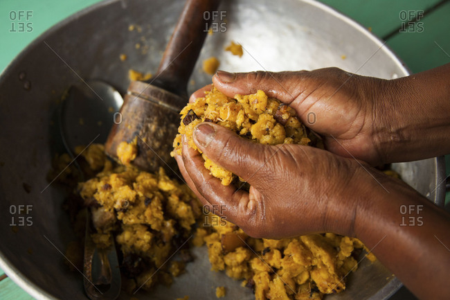 Hands mixing mashed plantain in a bowl
